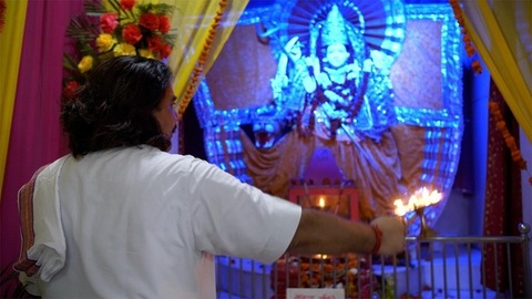 Still shot of a Hindu pujari in traditional clothing doing Aarti of Sherawali Mata idol in India