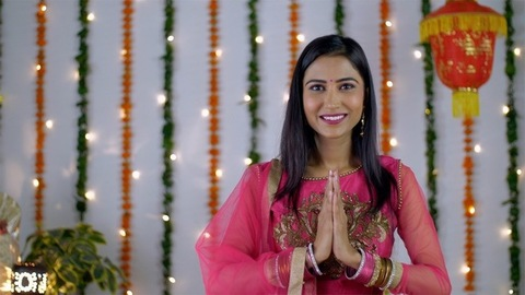 A young woman happily greeting in a traditional Indian namaste - colorful festive background