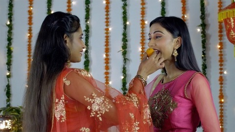 Two Indian females offering sweets to each other on the occasion of Diwali/Dipavali