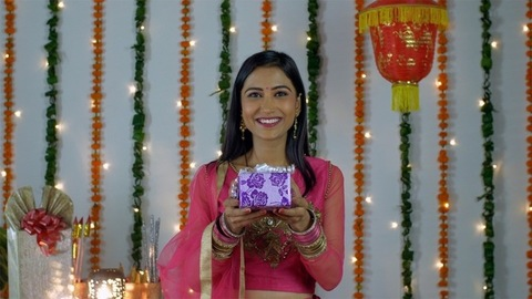 Beautiful young female happily smiling and showing a gift to the camera - Diwali festival