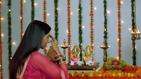 Beautiful Indian woman praying in front of Hindu gods Laxmi and Ganesh - Diwali/Dipavali