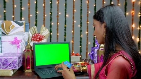 Bokeh shot of a pretty Indian woman doing online shopping for Diwali - the festival of India