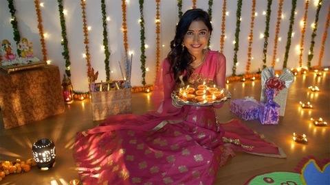 Beautiful Indian female smiling with burning Diyas on the festival of Diwali - decorative background