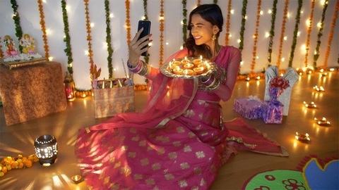 Pretty Indian lady enjoying while taking selfies with burning Diyas on Diwali festival