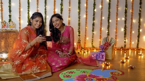 Two Indian sisters happily doing video call with a smartphone on Diwali festival