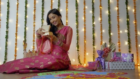 Beautiful Indian female opens her Diwali gift with a wide smile on her face - festive background
