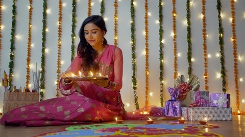 A young woman in traditional wear putting oil lamps on a colorful rangoli - Diwali
