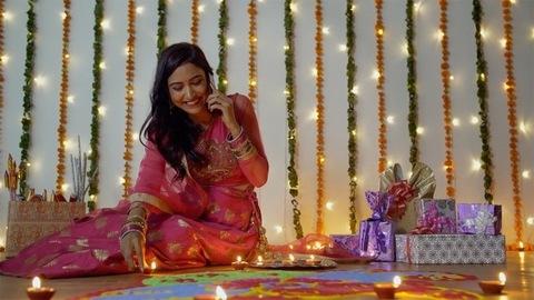 Pretty Indian lady decorating rangoli with burning Diyas - Festival of Diwali in India