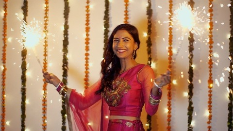 Beautiful young woman having fun with firecrackers in traditional clothing - Diwali festival