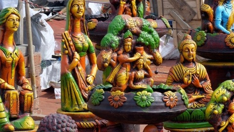 Pan shot of various decorated showpieces at a roadside stall for sale in India