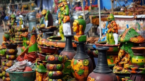 Pan shot of colorful clay decoratives out for sale in the festive market of India
