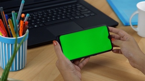 Woman hands using a black smartphone with a green screen during office time