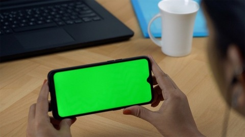 Woman hands using a green screen smartphone during office hours in India
