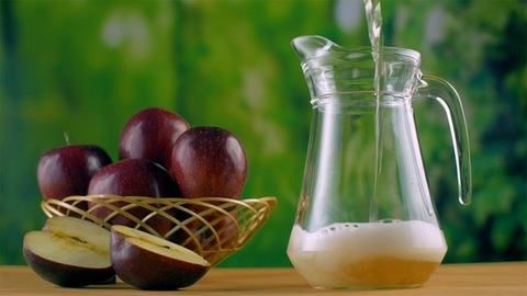 Still shot of pouring homemade apple juice into a glass jug or a container - healthy living