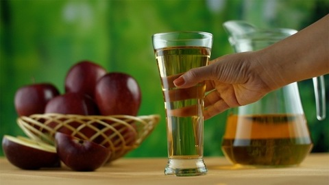Hands of an Indian lady takes away the glass of apple juice - healthy fruit diet