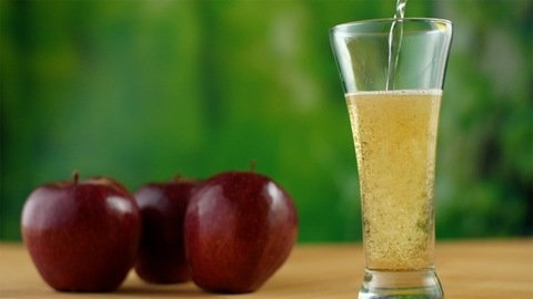 A glass of fresh apple juice with red apples on a wooden table - healthy diet concept