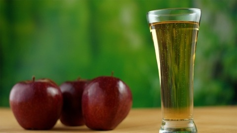 A glass of healthy fruit juice with red juicy apples placed on a wooden table