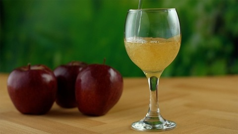 Closeup shot of pouring apple fruit juice into a wine glass - healthy beverage