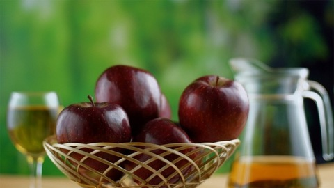 A basket of red juicy apples rotating clockwise on a turntable - healthy food concept