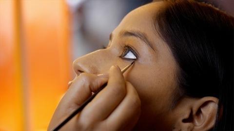Closeup view of an Indian makeup artist applying kajal to a model - makeup concept