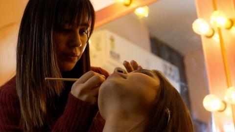 The young makeup artist is doing eye makeup of her client in her makeup studio