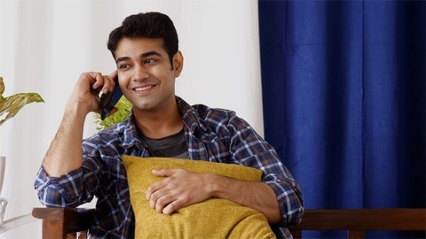 Young Indian man playfully talking on the phone while fidgeting with cushion