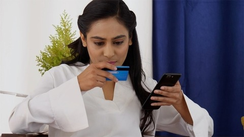Young Indian girl shopping online using her bank credit card / debit card