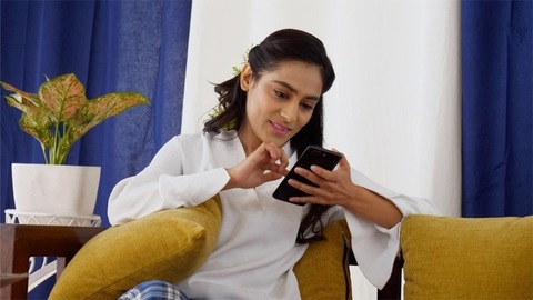 Happy Indian woman using her smartphone sitting on the sofa