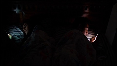 Indian boy and girl using their phones lying on bed before going to sleep - Technology in bedroom