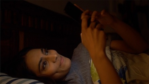 Young Indian girl chatting on phone late night before going to sleep