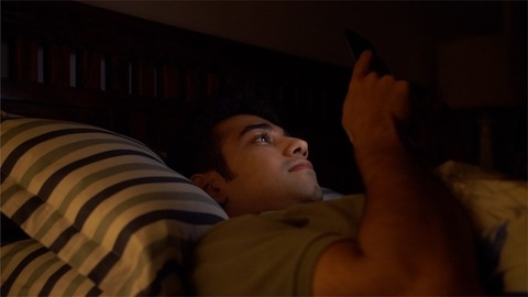 Young Indian guy chatting on smartphone late at night