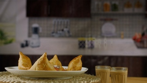 Still shot of a plate of delicious samosas served with masala chai(tea) in India