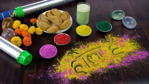 Woman hands writing 'Holi Hai' text on colorful Gulal during Holi celebrations in India