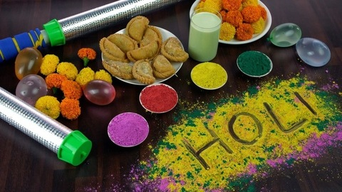 Woman hands placing a plate of homemade Gujiyas for Holi celebrations in India