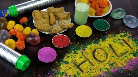 Indian female placing bowls of powder colors while preparing for Holi festival