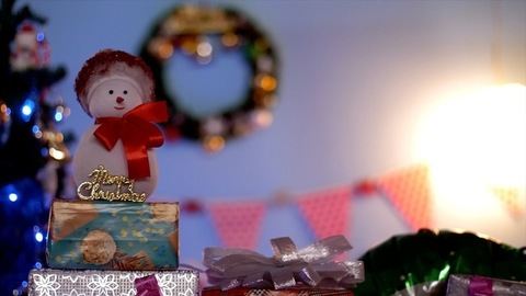 Pan shot of a decorated platform with colorful gifts and a smiling snowman on Christmas