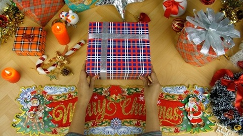 Hands of an Indian female putting a Christmas gift in the center of the decorated table