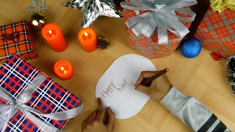 Hands of a young female writing 'Happy New Year' text on festive gift tags and cards