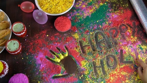 Hands of an Indian female writing 'Happy Holi' text on colorful Gulal - Holi festival