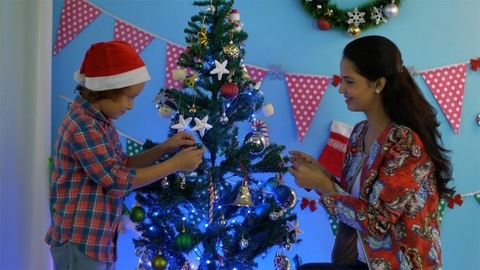 Happy Indian child in Santa hat cutely decorating Christmas tree with his mother