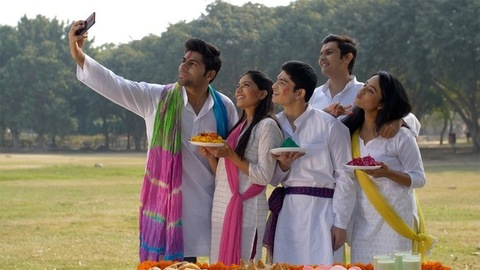 Young people in traditional wear smiling and posing for selfies at a Holi party in a park