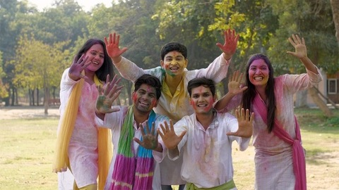 Group of cheerful young people happily wishing Happy Holi at a Holi party in a park
