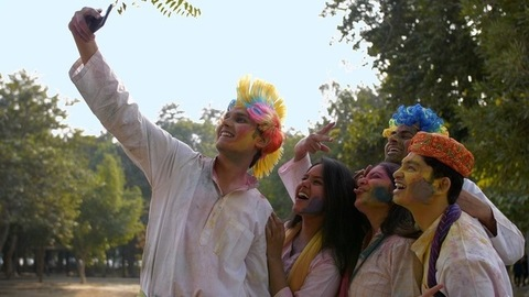 Young friends covered in Gulal colors taking selfies on a smartphone - Holi party