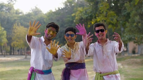 Young happy friends smeared in colorful Gulal enjoying the joyful Holi festival