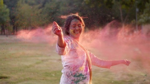 Smiling young girl in traditional clothing enjoying Holi festival celebrated in India