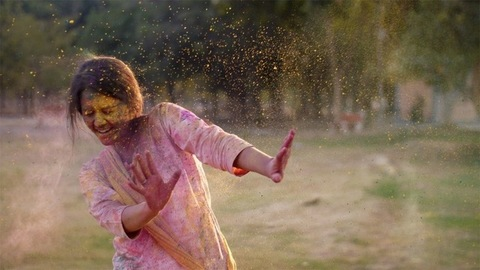 Young happy female having fun during Holi celebration - Indian festival and culture