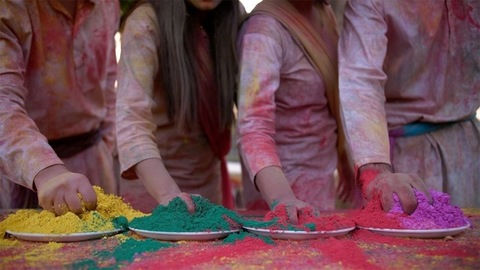 Closeup shot of young friends playing with colorful Gulal while celebrating Holi festival