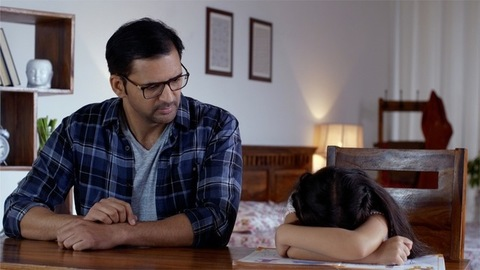 Indian father scolding his young daughter as she keeps her head down and cries - Depressed child and angry father