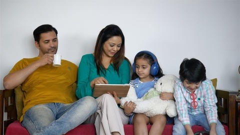 Indian family having a good time together while sitting on a sofa - leisure time