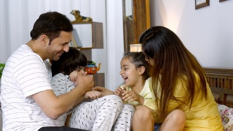 Young Indian couple laughing and enjoying with their kids - family leisure time